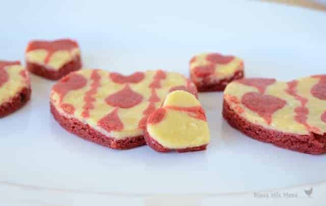 A close up shot of heart-shaped cheesecake bars on a white plate.