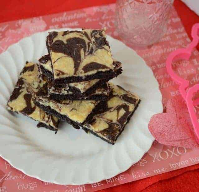 Cheesecake brownies on a white plate with a Valentine's day themed placemat.