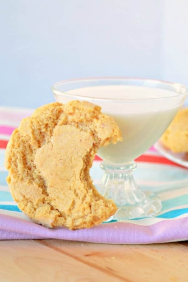 A peanut butter cookie with a bite out of it and leaned against a glass of milk