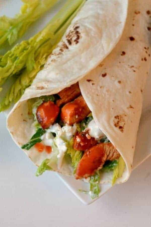 A wrap filled with lettuce, buffalo chicken and blue cheese dressing served with celery stalks on a square white plate