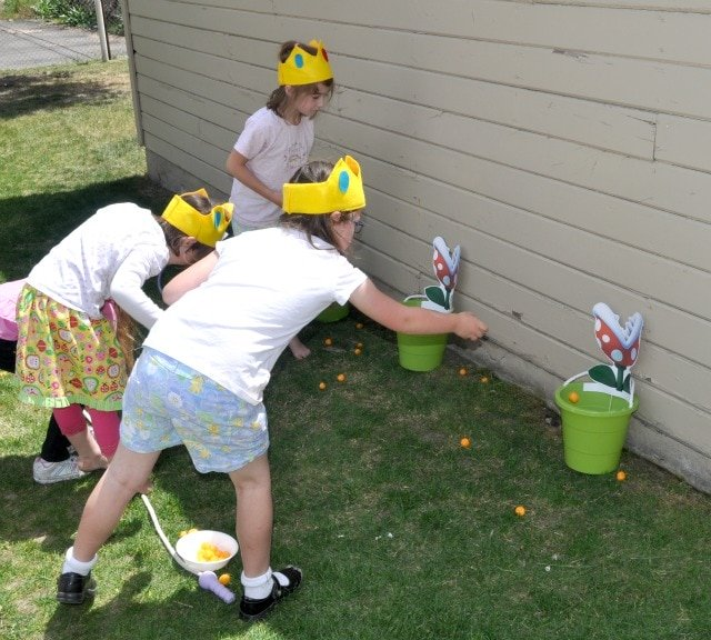 kids throwing balls into a bucket that looks like a piranha plant