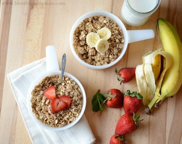 Homemade healthy granola in two bowls with bananas and strawberries and a glass of milk to the side