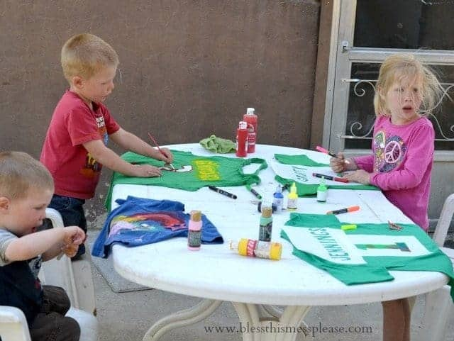 Three children sitting at an outdoor table working on a t-shirt craft project with stencils