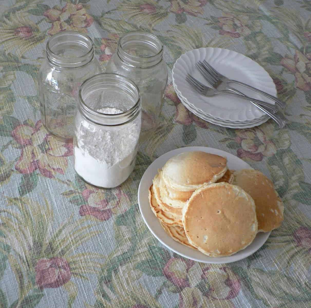 weekday pancake mix in a jar with cooked pancakes piled on a plate