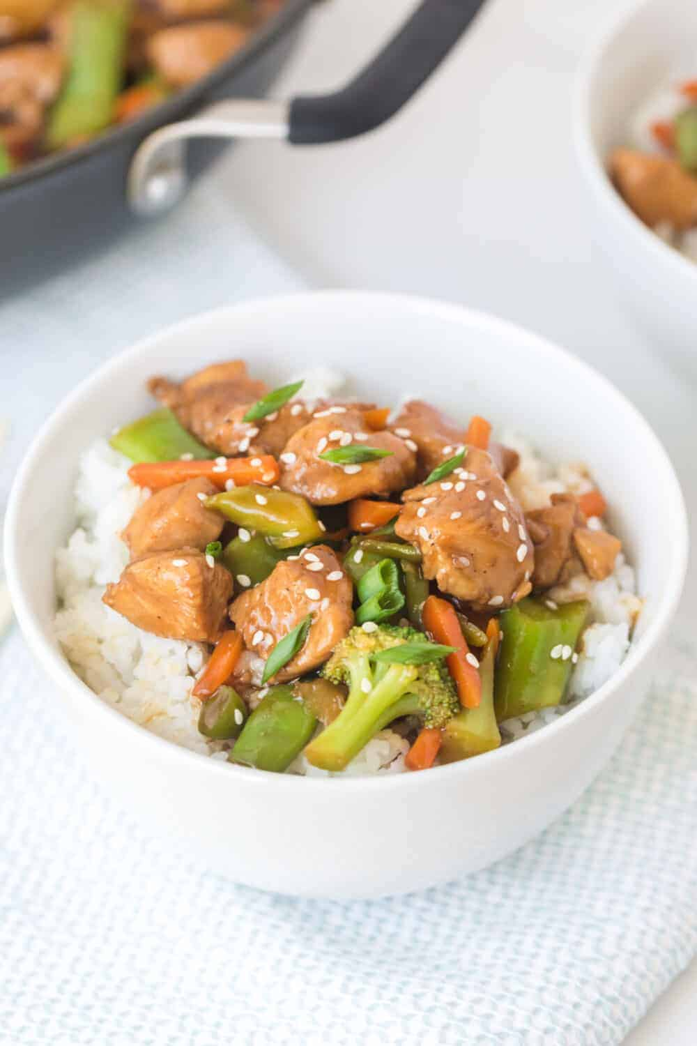 stir fry chicken and vegetables with white rice in a white bowl closeup