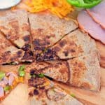 Ham and cheese quesadilla with diced green pepper cut into wedges on a wooden cutting board