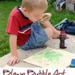 Title Image for Blown Bubble Art for kids with a little boy blowing green bubbles onto a sheet of paper on the sidewalk