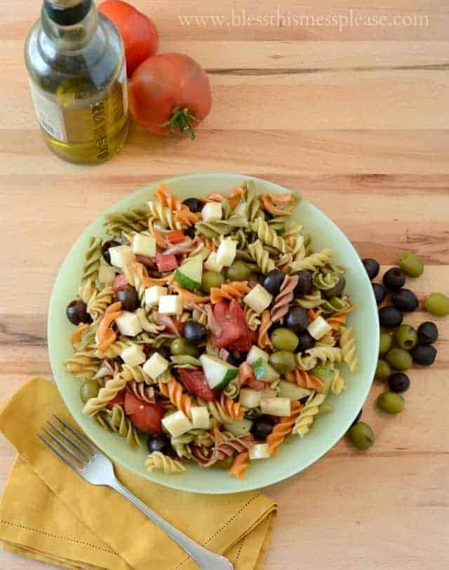 pasta salad in a green bowl with olives and tomatoes on the side