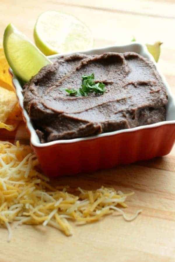 Refried beans in a red square dish garnished with fresh cilantro and a lime wedge