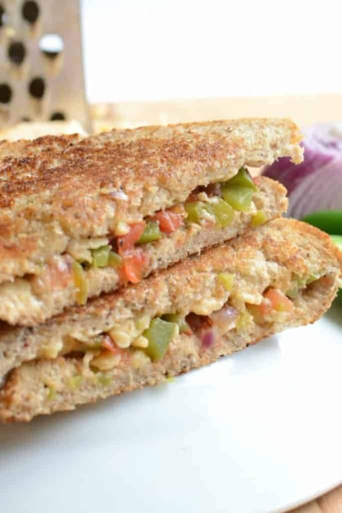 Two stacked triangles of grilled cheese sandwich with diced tomatoes, green peppers, and red onions