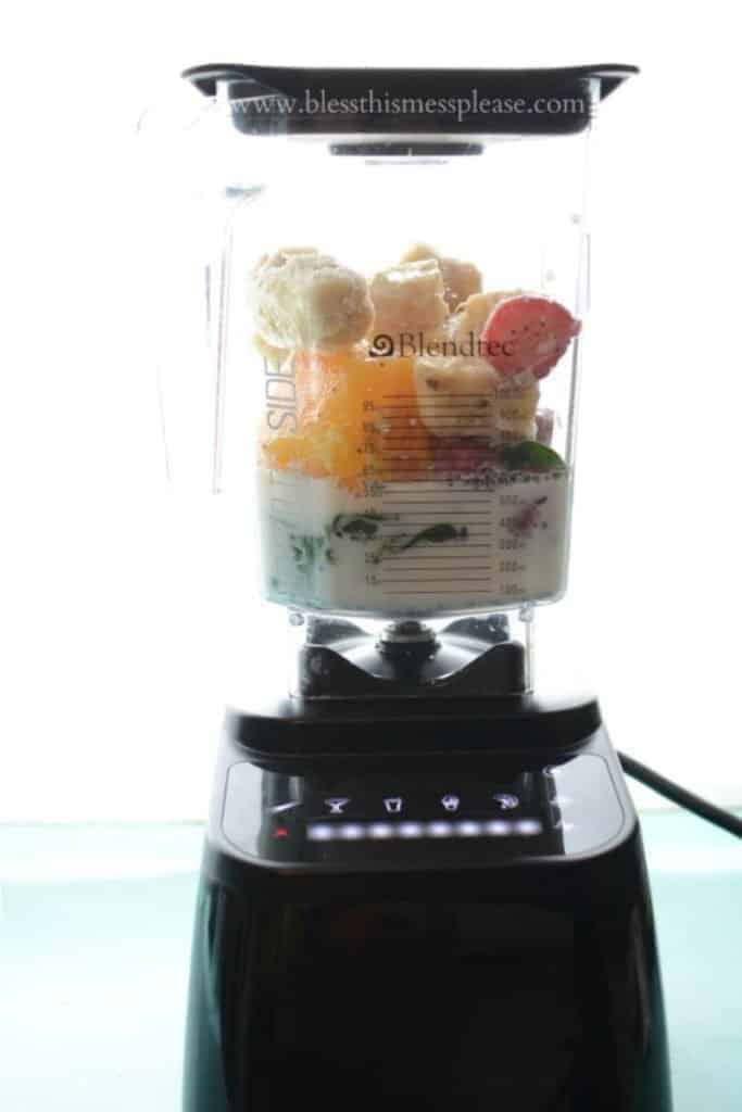 A blender filled with smoothie ingredients, including fruit, greens, and nut milk
