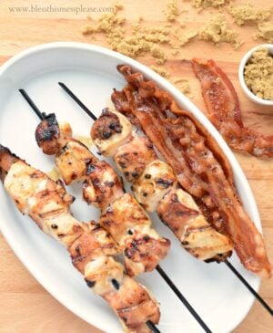 Plate of grilled bacon wrapped chicken skewers