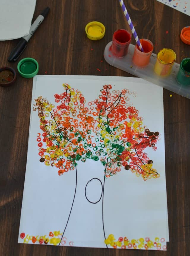 Kids fall artwork of a tree drawn on white paper with fall-colored small circles to represent leaves on the tree and ground