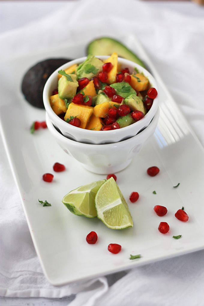 Pomegranate Mango Salsa in a white bowl with lime slices and pomegranate arils on the side.