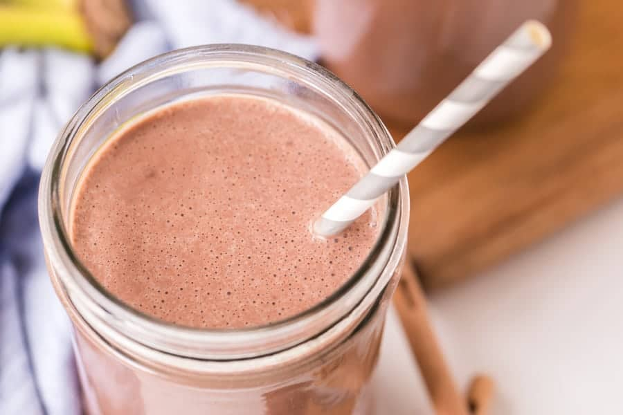 closeup of healthy peanut butter chocolate smoothie with gray striped paper straw