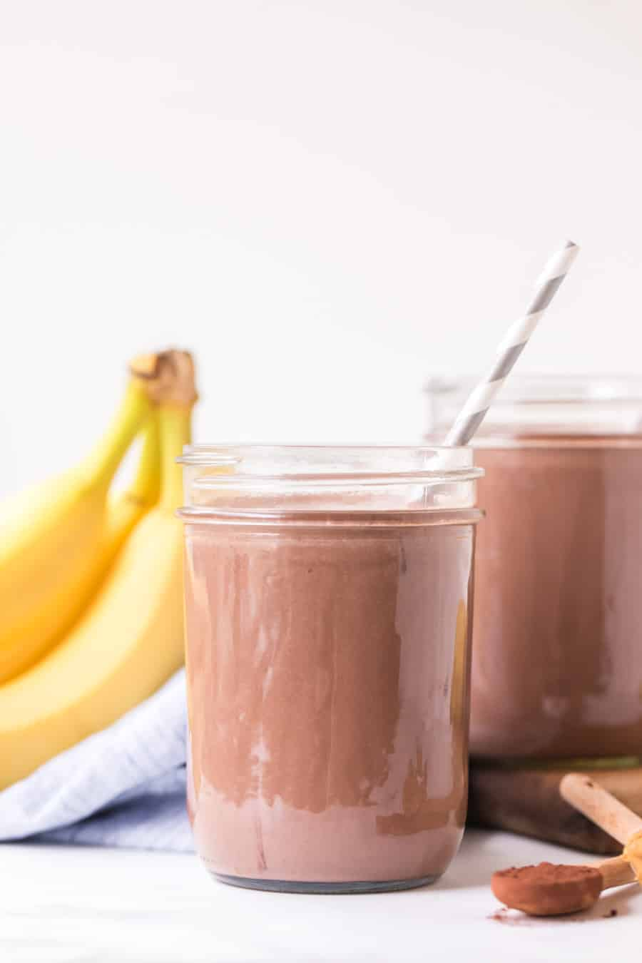 two glass canning jars filled with peanut butter chocolate smoothies with paper straws next to two bananas and teaspoon of cinnamon