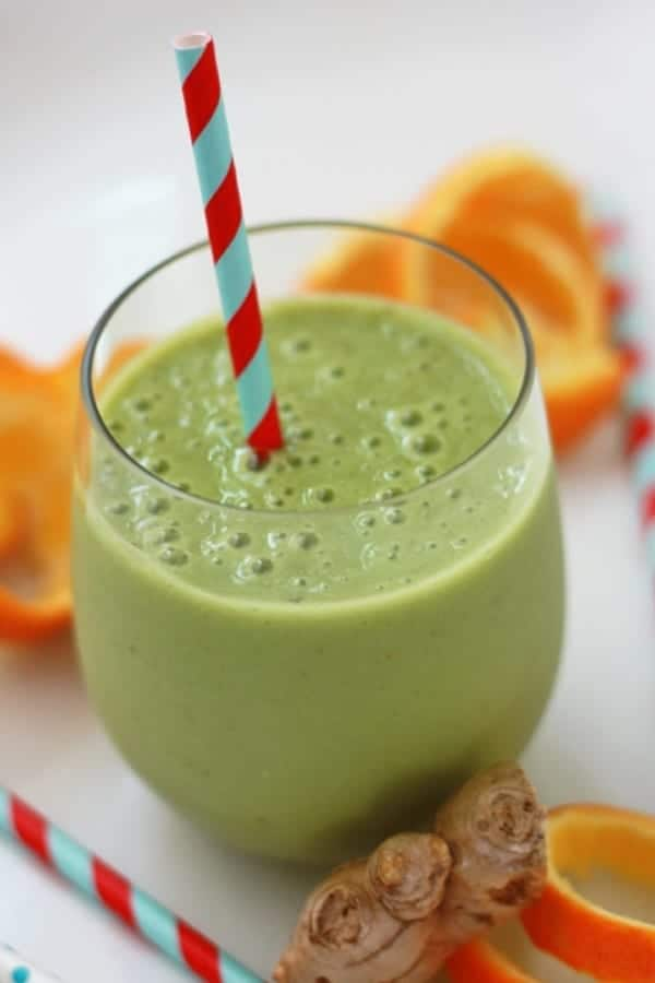 A clear glass of green smoothie with a striped straw