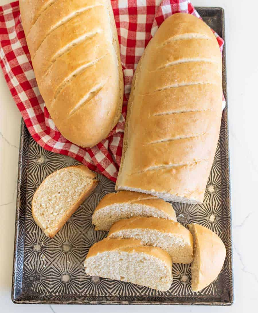 two loaves of french bread with slices of bread on tray with red checkered towel