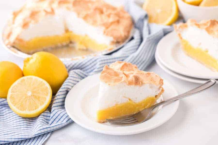 slice of lemon meringue pie on white plate with fork next to lemons and blue checkered towel