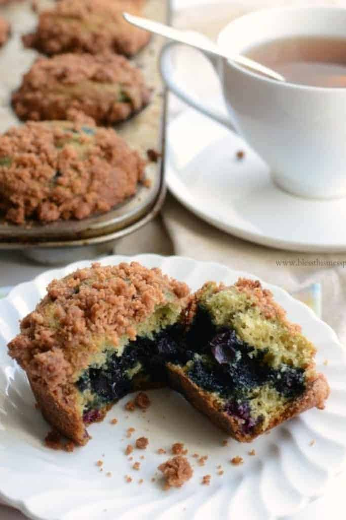 A blueberry muffin with crumb topping on a white plate with a cup of tea and a muffin tin of muffins in the background