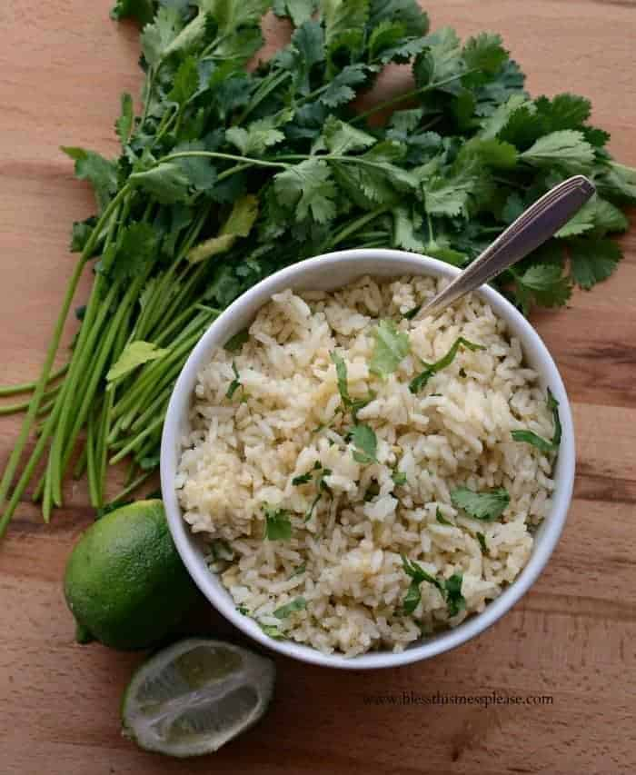 cilantro garlic rice in a white bowl with cilantro and lime on the side