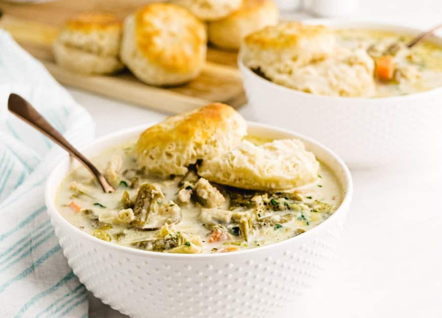 close up picture of a bowl of slow cooker chicken pot pie topped with a biscuit