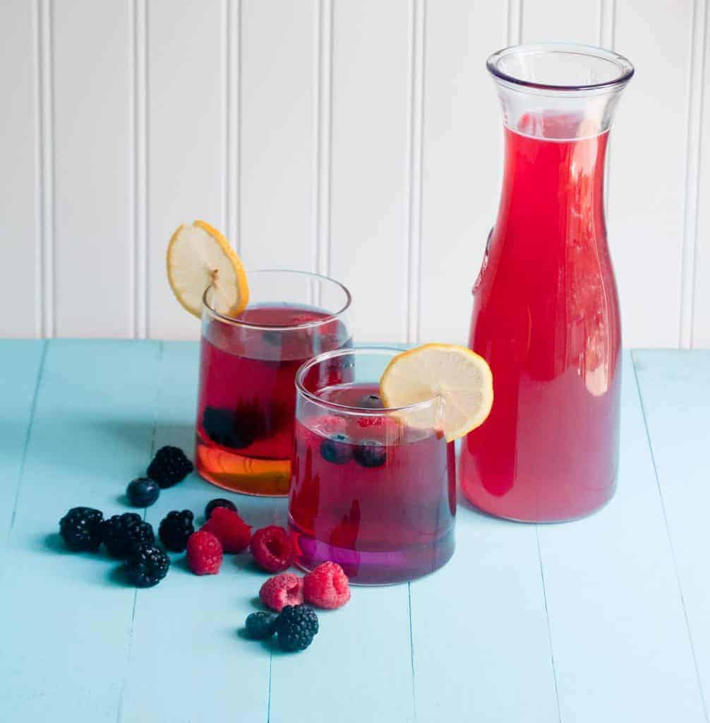 A carafe and two glasses of berry lemonade with fresh berries and lemon slices