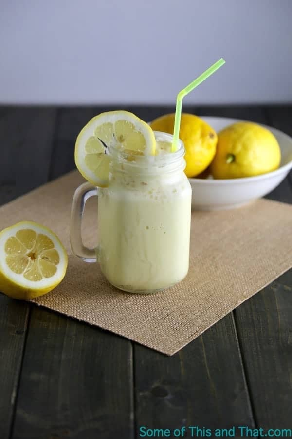 A mason jar of homemade frozen lemonade with a straw and lemon slice