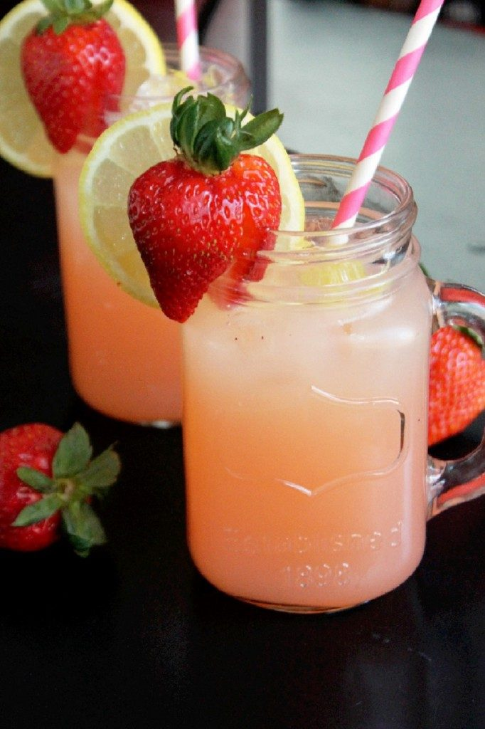 A mason jar of strawberry lemonade with fresh strawberry, lemon slice, and a straw