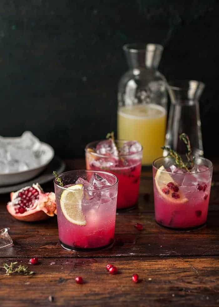 3 glasses of pomegranate lemonade with pomegranate arils and a sprig of thyme