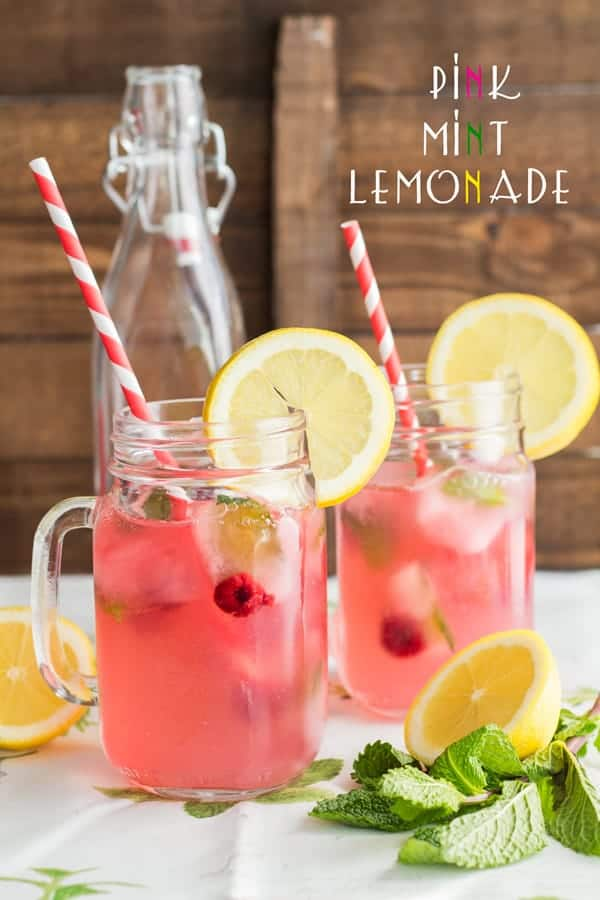 Two mason jars of Pink Mint lemonade with striped straws and a lemon slice on the rim of the glass