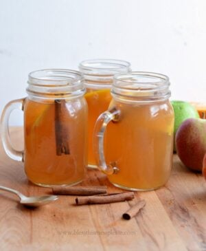 3 jars of slow cooker apple cider with fresh apples and cinnamon sticks