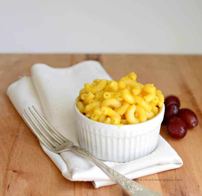 macaroni and cheese in a small white bowl with a napkin and fork to the side