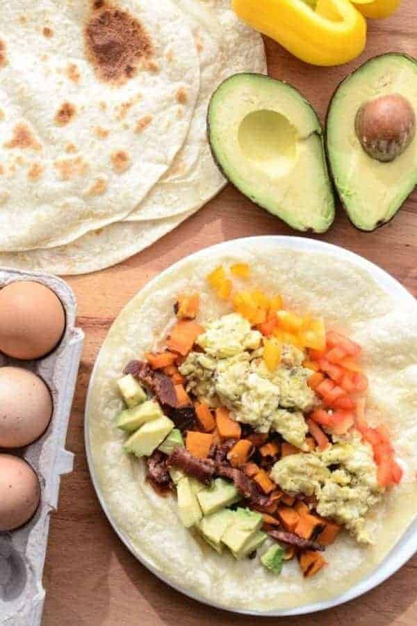 Quick, easy, and healthy Roasted Sweet Potato Breakfast Burritos made with roasted sweet potatoes, eggs, avocado and bacon. This recipe is done in 20 minutes and the perfect breakfast for dinner meal.
