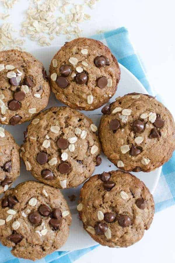 A batch of maple-sweetened banana muffins topped with chocolate chips and oats