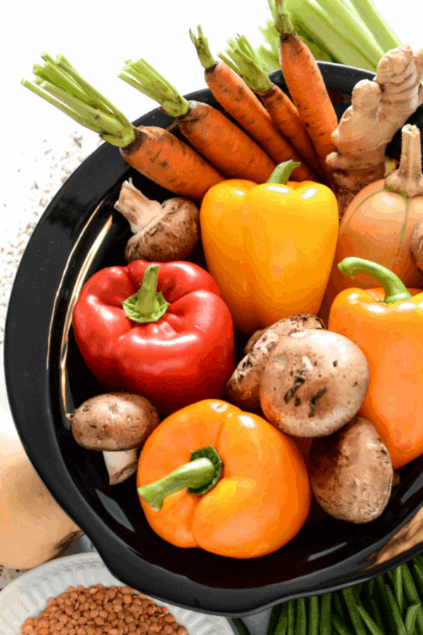Whole peppers, mushrooms and carrots, and other vegetables in a bowl