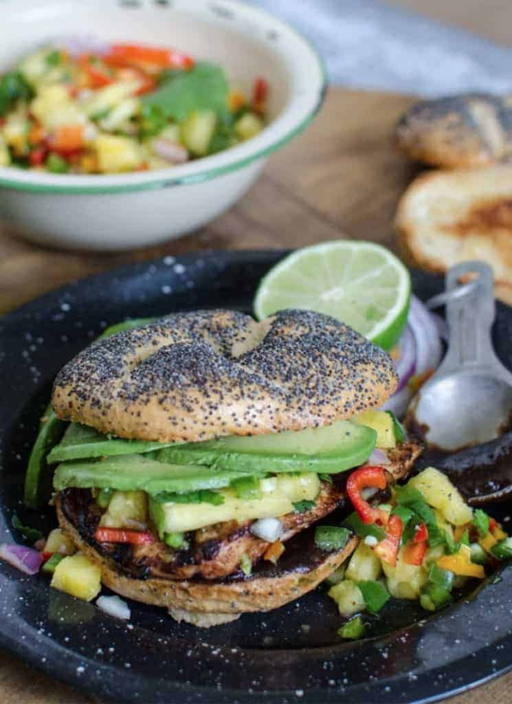 Grilled chicken sandwich with pineapple salsa and avocado, on a poppy-seed bun