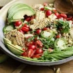 A large serving bowl of salad with sliced avocado, grilled corn kernels, grape tomatoes and sliced jalapenos