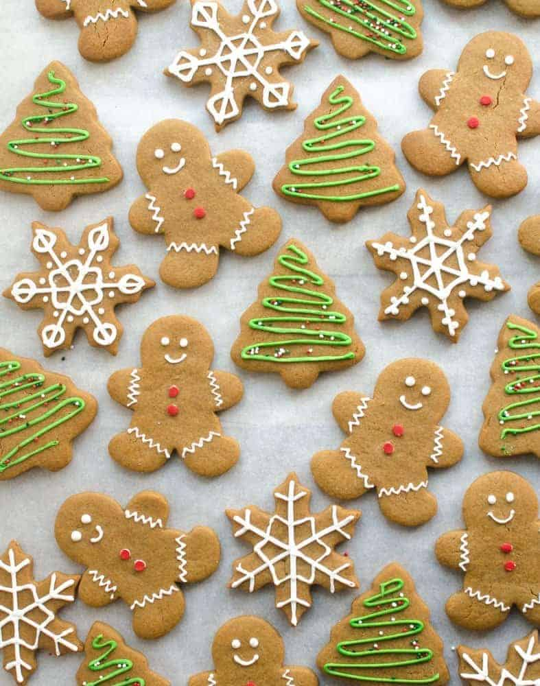 Gingerbread cookies that are shaped like men, trees, and snowflakes on a white background