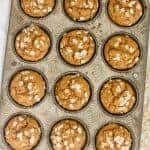 A dozen pumpkin muffins topped with oats in a muffin tins