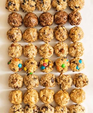 all 8 kinds of oatmeal energy bites all lined up in a 5 by 8 pattern on a white board
