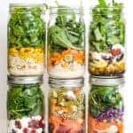 Six mason jars filled with different colorful layered salads
