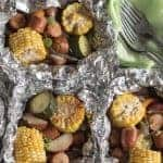 Foil packets with chunks of sausage, potato, zucchini and corn on the cob