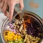 Dressing being poured over a mixing bowl of Asian Pasta Salad ingredients with colorful vegetables