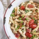 A white round serving bowl with chicken, bacon ranch pasta salad with halved grape tomatoes and green peas