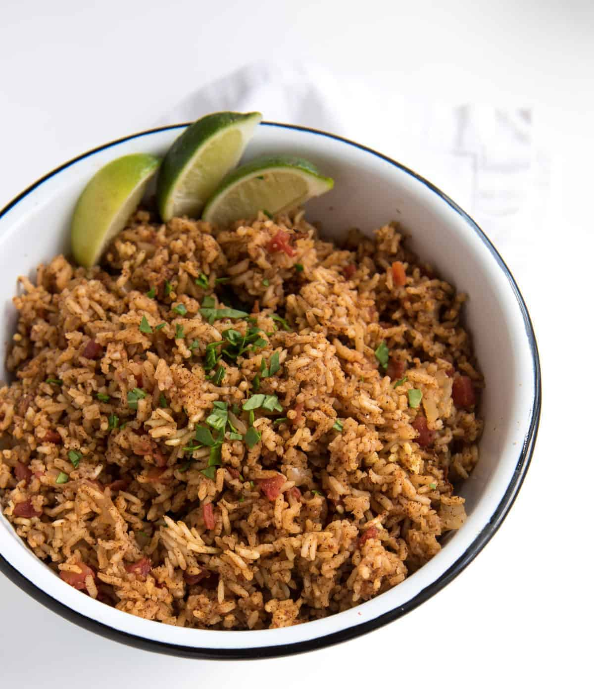 Such an easy & tasty rice cooker recipe! Spanish Rice made with a few simple ingredients (including a can of tomatoes). Just dump, mix, set it & forget it! #ricecooker #ricerecipes