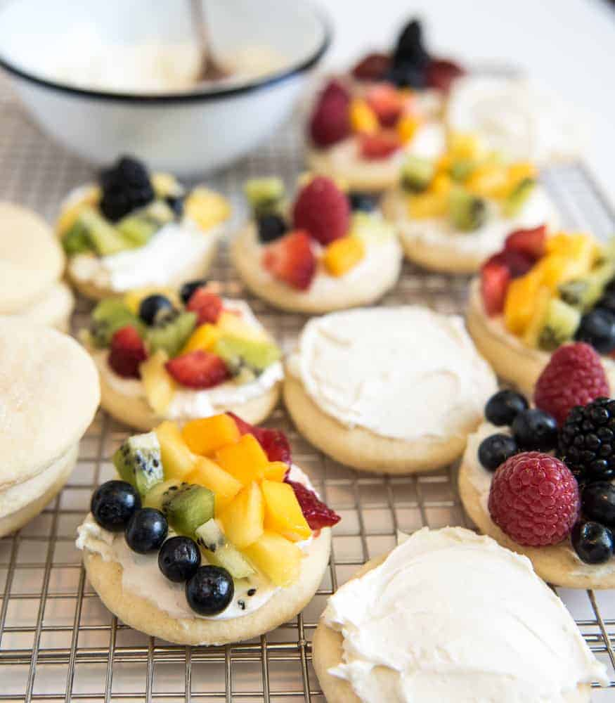 Festive fruit pizza cookies are made with super soft sour cream sugar cookies & a simple cream cheese frosting, & then piled high with seasonal fruit.