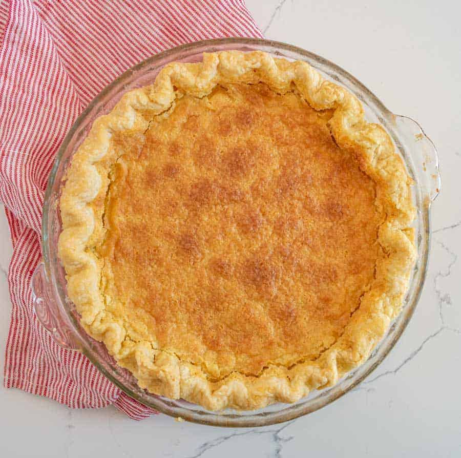 An old fashioned pie that has just been cooked is pictured. It is in a clear pie dish with a red and white striped towel underneath it.