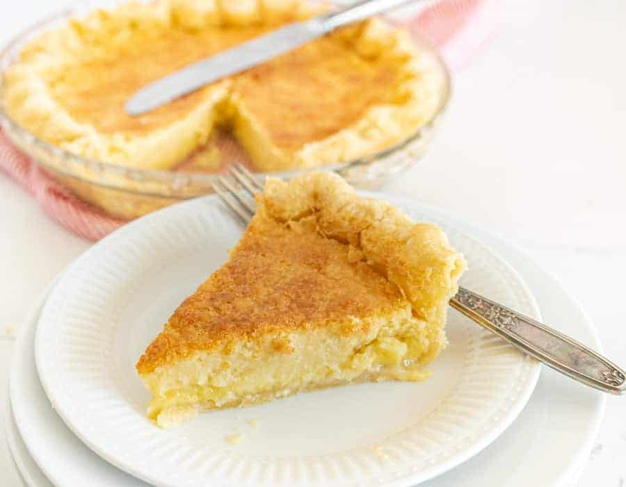 A slice of old fashioned buttermilk pie is on a white small plate with a fork in the foreground and in the background, the rest of the pie is in a clear pie dish with a butter knife on top of it.