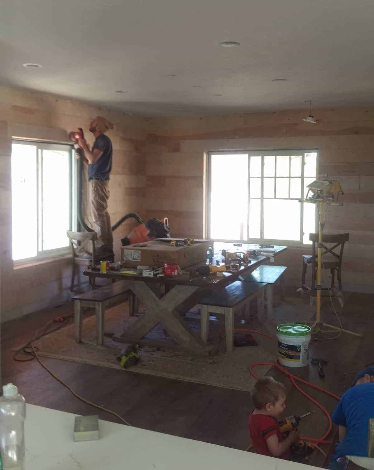 shiplap wood being installed on the dining room walls